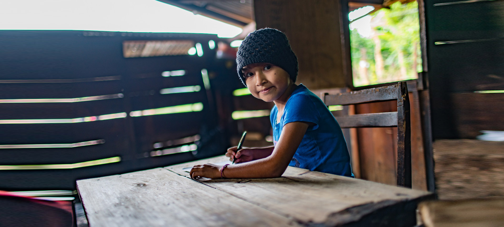 Young child smiling while sitting at a wooden desk